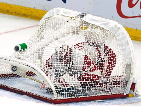 Detroit Red Wings goaltender Jared Coreau (31) is trapped underneath his net during the second period of an NHL hockey game against the Ottawa Senators in Ottawa, Ontario, Thursday Dec. 29, 2016.