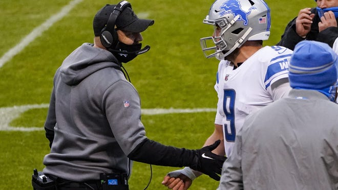 Detroit Lions head coach Darrell Bevell talks with quarterback Matthew Stafford (9) after he threw a touchdown pass against the Chicago Bears in the second half of an NFL football game in Chicago, Sunday, Dec. 6, 2020.