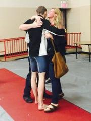 Ashland's Hudson McDaniel embraces his parents after