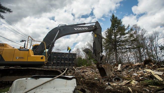 Crews work at a demolition site in the Rivercrest Historic District in Vestal in April 2015.