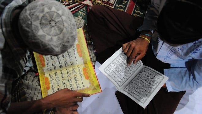 Men reading the Koran in Indonesia.