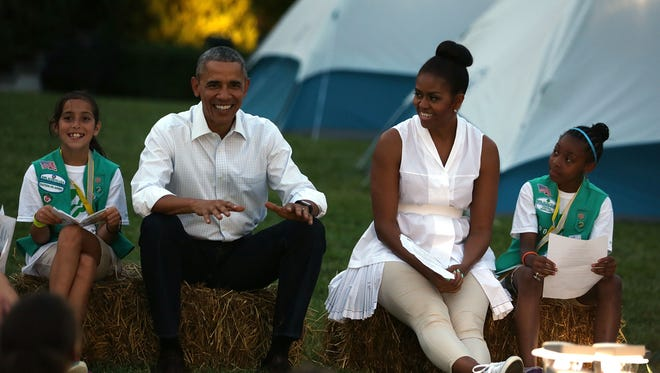 President and Mrs. Obama  are flanked by Daphnye Shell, left, of Peggs, Okla., and Kennedi Pridget, right, of Maryland, during the first-ever White House campout on June 30, 2015, on the South Lawn.