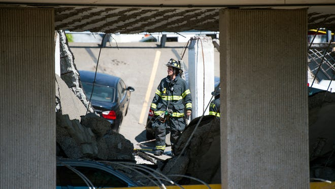 A firefighter stands where the upper-deck of a parking garage collapsed at UHS Wilson Medical Center in Johnson City on Thursday.