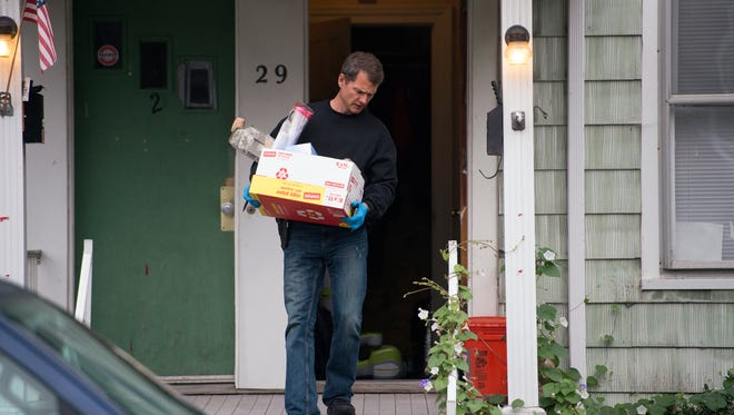 A DEA agent removes evidence from a home on Walnut Street in Binghamton following a drug bust Sept. 23, 2015.