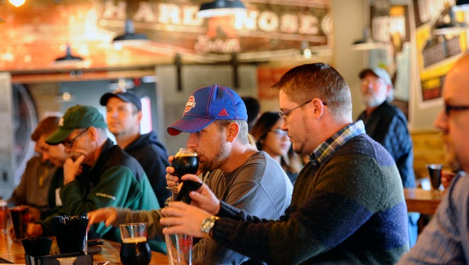 Patrons sample beers at the bar during  the grand opening of the Lansing Brewing Company in the Stadium District on Thursday.