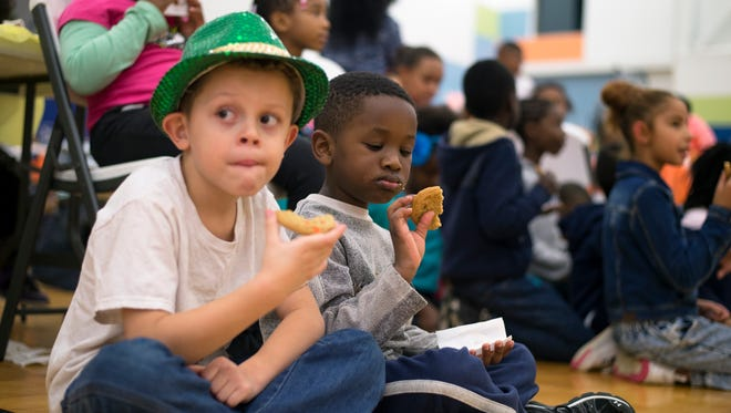 Right, Sheckna Traore, 5, of Binghamton and Erik Nandis Grijo, 7, of Binghamton, eat cookies after a Thanksgiving meal at the Boys and Girls Club of Binghamton on Tuesday, Nov. 24, 2015.