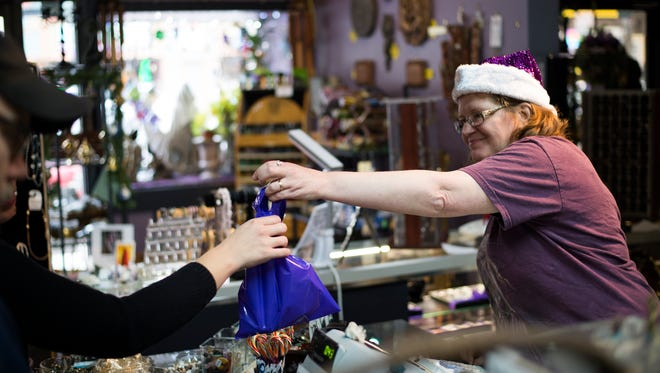 Imagicka employee Dawn Goldenberg rings up a customer during Small Business Saturday in downtown Binghamton.
