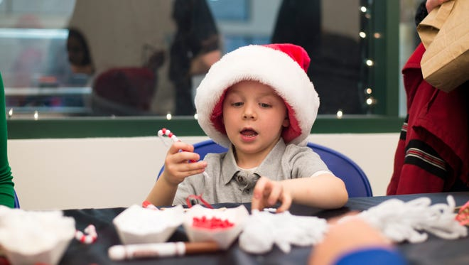 Three-year-old Landon Ryder, of Harpursville, makes a candy cane ornament out of pipe cleaner during the Reindeer on Ice event held at SUNY Broome on Saturday, Dec. 12, 2015.
