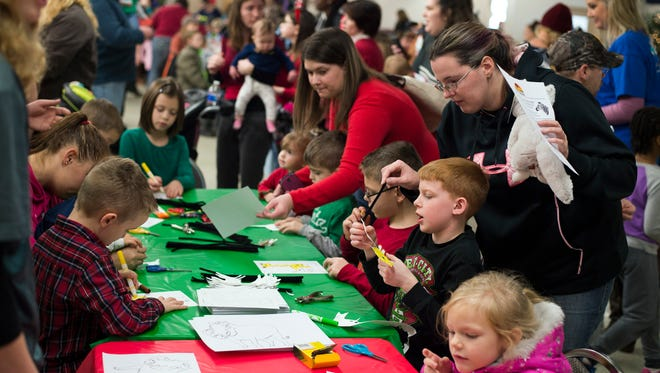 Children complete animal-themed holiday crafts during Animal Adventure's 4th Annual Jungle Bells event at Knights of Columbus in Binghamton on Saturday, Dec. 19, 2015.