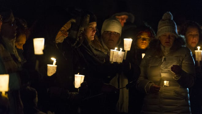 Hundreds gathered in the Brownsburg High School parking lot Sunday, Jan. 3, 2016, for a candle-light vigil to honor four Hendricks County teens — Matthew Chambers, Noah Tex, Lucas Kenworthy Sanders and Riley Hurst — who were killed in a car crash Wednesday.