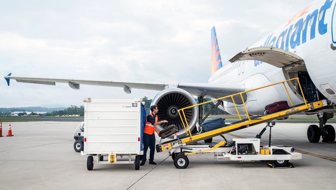 Dan Taha, supervisor with World Wide Flight Services, loads bags onto a ramp for an Allegiant Air flight from Asheville Regional Airport in August. Allegiant on Tuesday announced new service to the Washington, D.C., area.