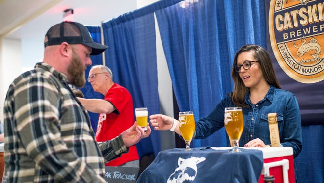 Gretchen Hartman, a representative for Catskill Brewery, serves a beer sample during Binghamton On Tap at the DoubleTree Hotel in downtown Binghamton on Saturday.