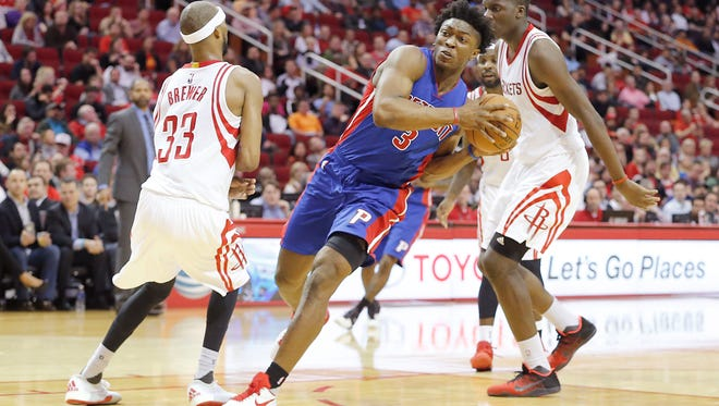 Pistons forward Stanley Johnson (3) splits the defense of Rockets guard Corey Brewer (33) and forward Clint Capela (15) in the second half of the Pistons' 123-114 win Wednesday in Houston.