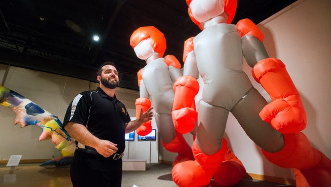 """Jason Fiume, marketing and public-relations manager for the Roberson Museum and Science Center, with """"Inflatable Superheroes,"""" by artist Patrick Flibotte."""