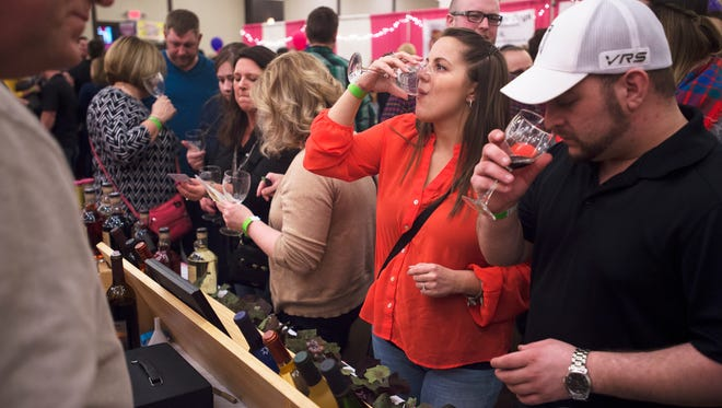 Nicole Kraeger, center, and her fiance Chris Allen, both of Binghamton, sample wines from Raymor Estate Cellars during the first Binghamton Wine and Chocolate Festival on Saturday.