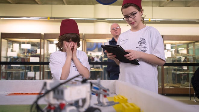 Sidney Elementary students Althea DeVost, 10, on left, and SaraBeth Clupper, 11, pilot their robot through a forklift challenge during the Southern Tier Robotics Competition at SUNY Broome on Wednesday, March, 16.