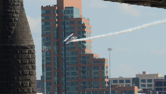 A single prop bi-plane maneuvers over the Ohio River in front of the Louisville skyline during the Thunder Over Louisville air show.