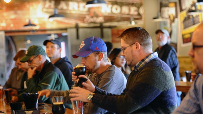 Patrons sample beers at the bar during the grand opening of the Lansing Brewing Co. in the Stadium District.