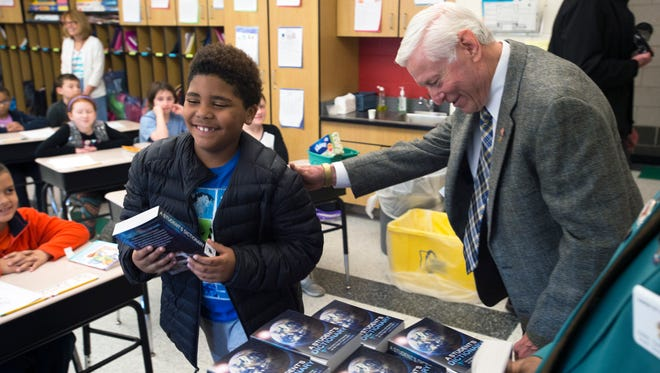 Eight-year-old Ryshon Carney smiles after receiving a free dictionary from Johnson City Rotary President Ron Heebner at Johnson City Intermediate School on Wednesday. The rotary and elks clubs teamed up to donate nearly 400 dictionaries to third and fourth grade classes at the school.
