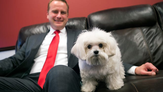 Broome County District Attorney Steve Cornwell in his office with his 5-year-old maltese, Bean, who often accompanies Cornwell to work and comforts children involved in criminal cases.