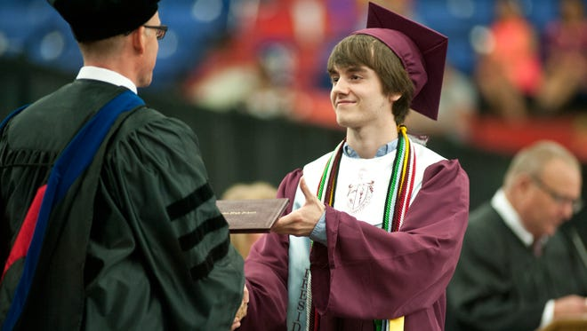 Jeffersontown High School Class of 2016 president Sean Meredith, one of thirteen valedictorians, is the first to receive his diploma from school principal Matthew Kingsley. 28 May, 2016