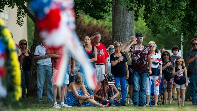 """Citizens and veterans listen as """"Taps"""" is played during a Memorial Day wreath-laying ceremony on Monday, May 30, 2016 at the Autauga County Courthouse in Prattville, Ala."""