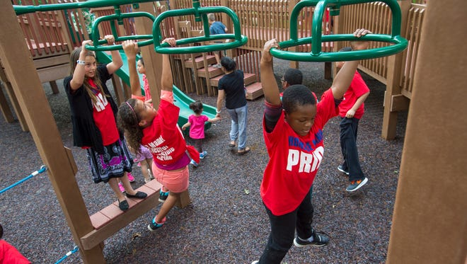 Elementary students from Horace Mann Elementary play on the monkey bars Tuesday at the OurSpace Park playground during the park's opening day.