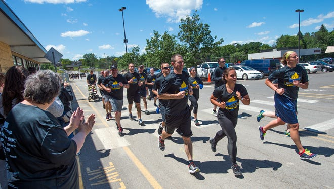 Local law enforcement and Special Olympics athletes run side-by-side Thursday to raise awareness and funds for the Special Olympics during a torch run in Vestal.
