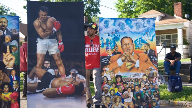 Terry Wilson of Indianapolis stands between two of his paintings while outside the boyhood home of Muhammad Ali on Grand Avenue.