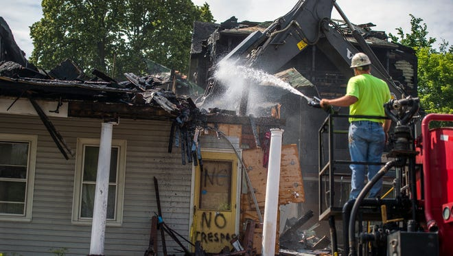 Crews demolish the fire-damaged home at 162 Henry St. in Binghamton on Thursday.