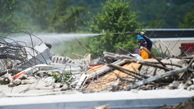 A worker sprays debris with water Saturday during the demolition of the former Ken Wilson Chevrolet dealership on the Vestal Parkway.
