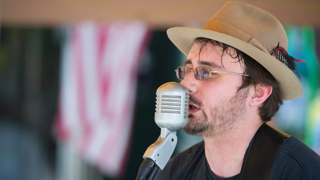 Joel Huizinga, of Chenango Forks, sings with his bluegrass band Melanie and the Boys during the Owego Strawberry Festival on Saturday.