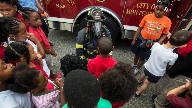 Michael Johnson of the Montgomery Fire Dept. wears firefighting gear for children during a presentation at Dannelly Elementary School on Tuesday, Jun. 28, 2016 in Montgomery, Ala.