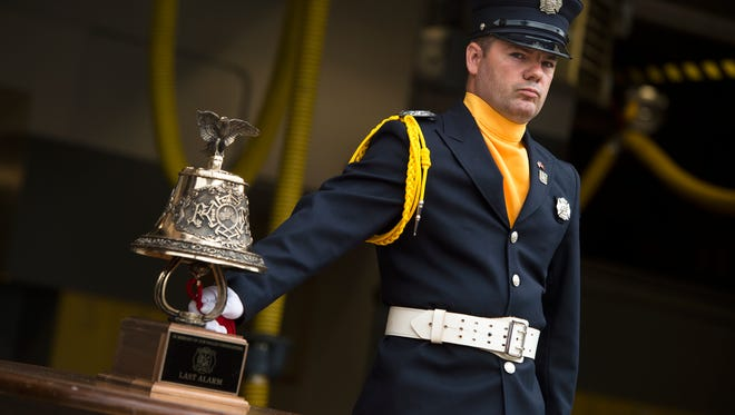 """Binghamton firefighter Ron Mason rings the """"last alarm"""" to memorialize firefighters who have died over the past year during a memorial ceremony Wednesday in Binghamton."""