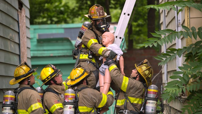 Lieutenant Jeff Allen hands a dummy down to fellow Binghamton firefighters during a training excercise at 17 Mygatt St. in Binghamton on Friday. The firefighters used the abandoned buildings to practice rescue scenarios, using a machine to simulate smoke.