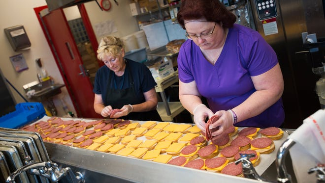 Jennifer Anderson of Endicott, right, and Linda Nugent of Kirkwood prepare salami sandwiches for students who need meals during the summer months at Binghamton High School on Wednesday, July 6.