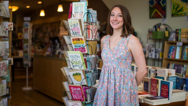 Artist Katie Vaz, 28, with cards she illustrated at RiverRead Books in Binghamton.