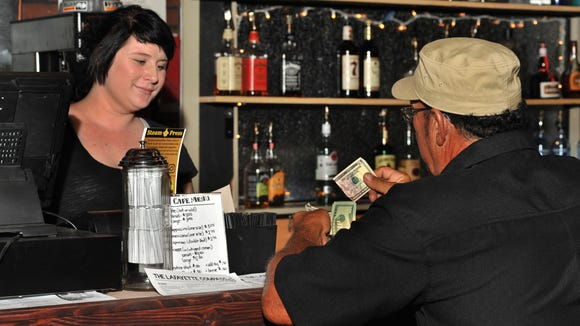 Barista Steeva Montcalm serves a customer at Steam Press Cafe in downtown Lafayette.