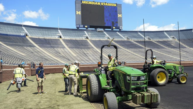 Workers install real grass at Michigan Stadium for Saturday's match between Chelsea and Real Madrid Monday in Ann Arbor.