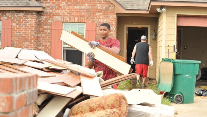 Ragin' Cajuns football players help demo a flooded home in Youngsville, LA after the flood of 2016