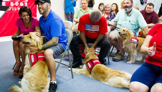 From left, Reid Erickson and his wife Zulma, Raymond Dillman, and Marty Monkiewicz, greet their new dogs at PAWS in Naples during a certificate program on Friday, Aug. 26, 2016. PAWS Assistance Dogs, Inc. provides fully trained and certified service dogs to combat-wounded American veterans and children with disabilities. PAWS dogs spend up to two-and-a-half years in an intensive training program that includes socialization, obedience and detailed task training.