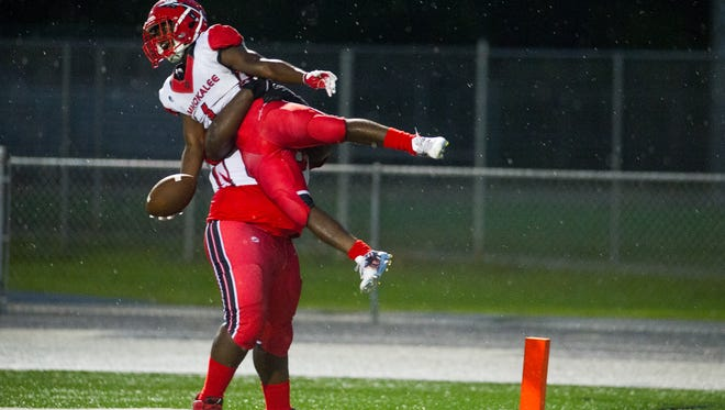 Immokalee High School's Fredrick Green (1) gets picked up by his teammate Emmanuel Augustin (62) during a game against Golden Gate on Friday, Aug. 26, 2016.