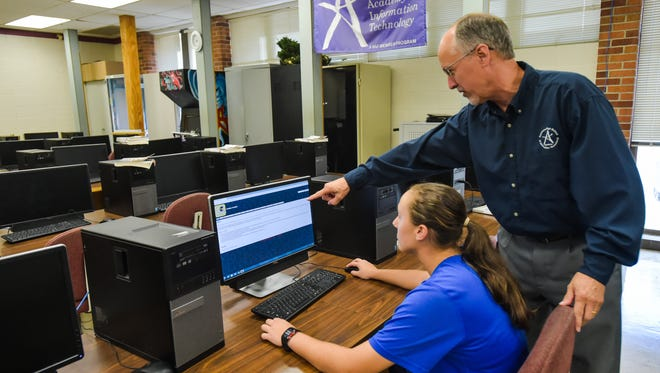 Carencro High School  computer technology teacher Joel Hilbun and project student Danielle Heim view the website his class researched and produced that chronicles 50 years of Carencro High football in the LHSAA.