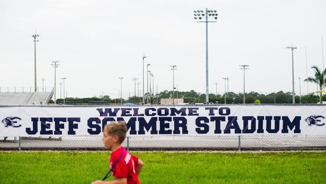 A kid runs past a sign for the new Jeff Sommer Stadium during the dedication to Coach Jeff Sommer at Estero High School on Friday, Sept. 2, 2016.