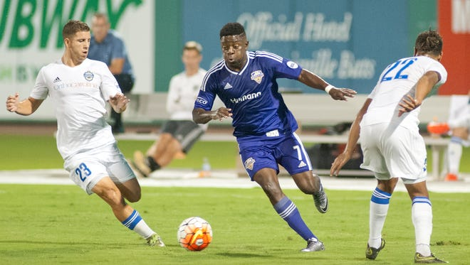 Louisville midfielder Kadeem Dacres moves the ball between Charlotte forward Alex Martinez, left, and defender Joel Johnson, right.24 September 2016