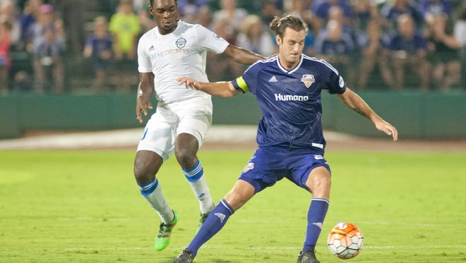 Louisville midfielder Paolo DelPiccolo keeps the ball away from Charlotte forward Brian Brown. 24 September 2016