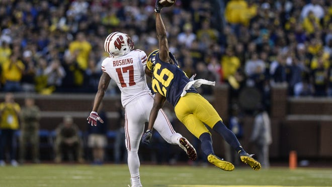 Michigan's cornerback Jourdan Lewis (26) intercepts a pass intended for Wisconsin wide receiver George Rushing in the fourth quarter of U-M's win Saturday at Michigan Stadium.