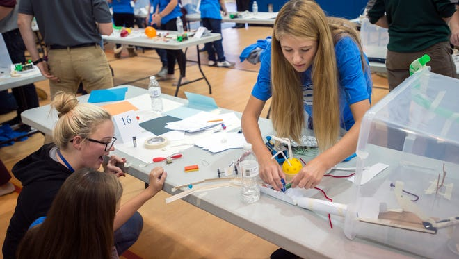 Whitney Point Middle School student Haydyn Bechtel, 13, right, tinkers with her team's Rube Goldberg machine Thursday during Engineering Day at Broome-Tioga BOCES.