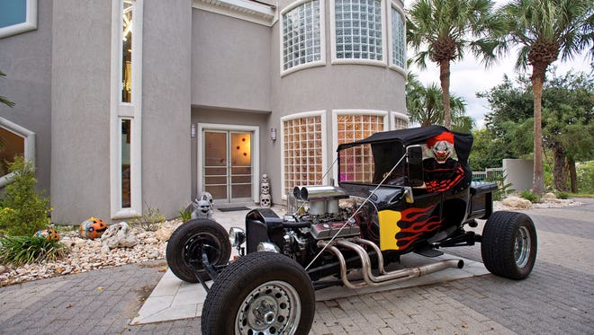 A scary clown and his hot rod in front of the Kaufmann's ultra contemporary home