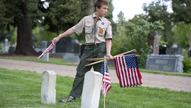 Quentin Kurtz, 13, of Boy Scout Troop 188, places American Flags on the graves of W. W. Westfall and Robert Ayers in Grandview Cemetery in 2014. The men, as well as other Camp Collins soldiers, will be honored with a monument Saturday.